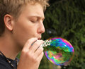 Blowing big rainbow bubble Stock Images