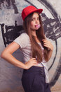 Blowing bubblegum trendy beautiful long haired model posing on graffiti background blow red cap grey t shirt Stock Image