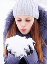 Blowing on snow young girl in their hands Stock Photo