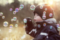 Blowing soap bubbles little boy playing with bubble wand Royalty Free Stock Images