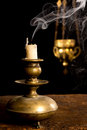 Blown out candle in antique stick and in the background a blurred incense thurible Royalty Free Stock Photos