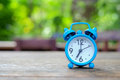 Blue alarm clock on wooden with green blurred back Royalty Free Stock Photo