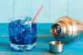 Blue alcohol or alcohol free cocktail with straw ice cubes and shaker on a light wooden background Royalty Free Stock Image