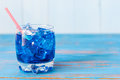 Blue alcohol or alcohol free cocktail with straw and ice cubes on a wooden table empty space for text Stock Photos