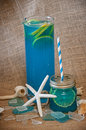 Blue alcohol drink this is a with lemon and seashells with broken glass good for a beach look Stock Photo