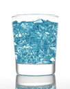 Blue artificial ice in water glass isolated white background Royalty Free Stock Photos