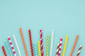 Blue background with colorful paper straws for cocktails. Royalty Free Stock Photo