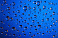 Blue background of water droplets on the glass Royalty Free Stock Photo