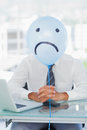 Blue balloon with sad face hiding businessmans face in bright office Stock Photos