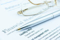 Blue ballpoint pen and eye glasses on a company's financial analysis check list. Royalty Free Stock Photo