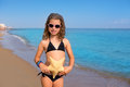Blue beach girl with bikini starfish and sunglasses Royalty Free Stock Photo