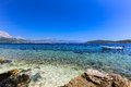Blue beach at Korcula Croatia with boat and swimmers Royalty Free Stock Photo
