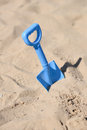 Blue beach shovel stuck in sand by a child the Royalty Free Stock Photography