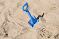 Blue beach shovel stuck in the sand by a child Stock Photos