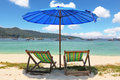 A blue beach umbrella and striped chaise lounges Stock Images