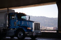 Blue big rig semi truck with tank trailer running on lower floor Royalty Free Stock Photo