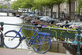 Blue bike parked on bridge over Amsterdam canal Stock Image