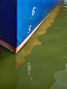 Blue boat hull and reflection in water a bright with the numbers it s on the surrounding Royalty Free Stock Photo