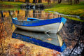 Blue boat on the lake in autumn forest colorful landscape nature background old wooden bank Stock Image