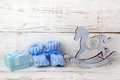 Blue booties for the baby on a wooden background of blue gift box with satin ribbon and wooden horse. Royalty Free Stock Photo