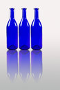Blue bottles with reflection isolated on white background Royalty Free Stock Photo