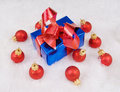 Blue box with red bow and red spheres Stock Photography
