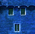 Blue brick wall with windows Stock Images