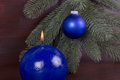 Blue burning candle on christmas blute chritmas with ball and fir branch with dark wooden background Royalty Free Stock Photography