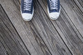 Blue canvas sneakers on feet on wood person in shoes standing a gray wooden floor Royalty Free Stock Images