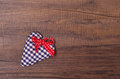 Blue checkered heart with red ribbon on a wooden board Royalty Free Stock Photo
