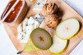 Blue cheese with slices of pear nuts and honey on bamboo wooden cutting board Royalty Free Stock Images