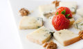 Blue cheese with strawberries and walnuts on a white background Stock Image