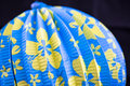 Blue chinese paper lantern with bright yellow flowers isolated up close on black background Royalty Free Stock Photography