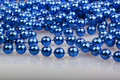 Blue christmas beads on white Stock Photography