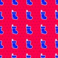 Blue Christmas stocking icon isolated seamless pattern on red background. Merry Christmas and Happy New Year. Vector Royalty Free Stock Photo