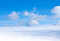 Blue cloudy sky and snow field in winter day Royalty Free Stock Photography