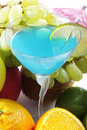 Blue cocktail among fruits Royalty Free Stock Photography
