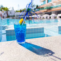 Blue cocktail with its shadow and poolside straw near the pool Stock Photo