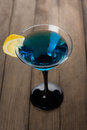Blue cocktail in martini glass with slice of lemon Royalty Free Stock Photo