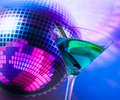 Blue cocktail with sparkling disco ball background with space for text Royalty Free Stock Photo