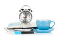 Blue coffee cup, alarm clock and office supplies Stock Images