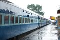 Blue color coaches of indian train stainding in a station during rain Royalty Free Stock Photos