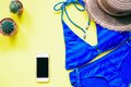 Blue color swimwear with smartphone, cactus and hat flat lay on yellow background, Summer vacation Royalty Free Stock Photo