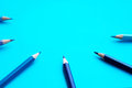 Blue colored pencils in a semicircle - blue background