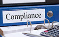 Blue compliance binder a with the label with office supplies on a desk Stock Images