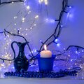 Blue composition with candle and miniature mug, blue pearl ornaments in the foreground, white and blue light chain background, Royalty Free Stock Photo