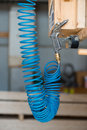 Blue compressed pneumatic air hose with pistol hanging at screw Stock Photo
