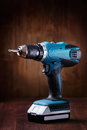 Blue cordless screwdriver with a drill on wooden table with wooden background Royalty Free Stock Photo