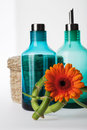 Blue cosmetic product bottles and a basket two wicker an orange gerbera flower Stock Image
