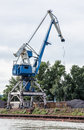 Blue crane in cargo port translating coal industrial scene big vertical composition Stock Photos